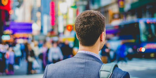 Male Millennial in a suit searches through a crowded street