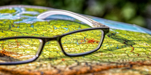 reading glasses on a map representing someone comparing international insurance companies