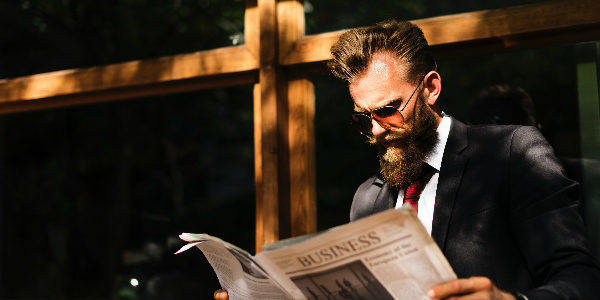 Corporate man reads the business pages outside a coffee shop, symbolizing how people are interested in reading about employee benefits and staff retention