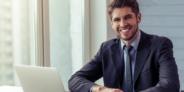 an employee benefits broker smiles warmly from behind his desk