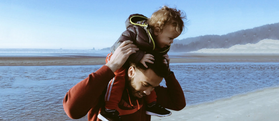 a child rides his father's shoulders on the beach signifying the need for companies to consider employee life insurance to protect loved ones