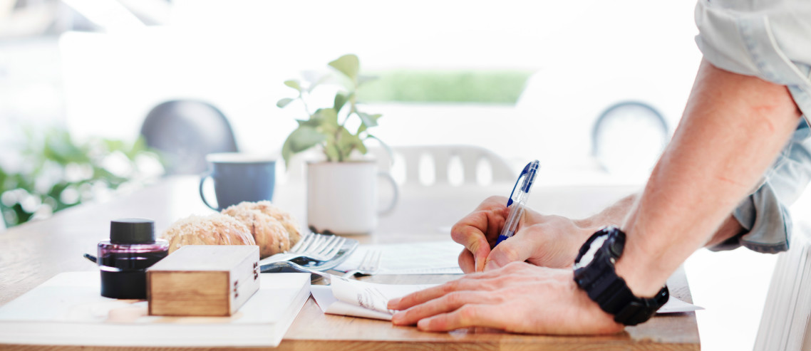 a man checks off a list on a table covered with healthy food and papers, symbolizing his company creating a wellness program for their staff