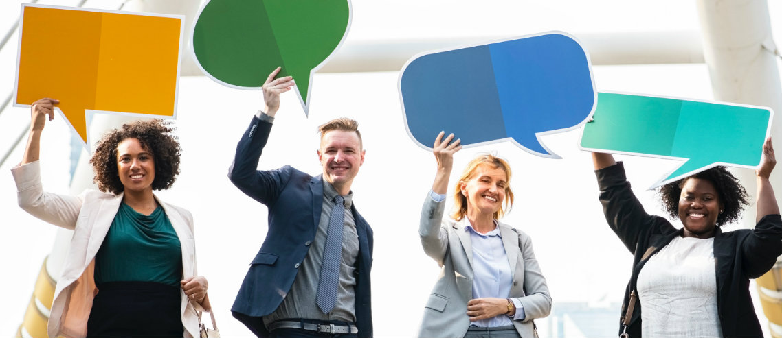 a diverse group of professionally dressed employees hold up feedback speech bubbles symbolizing the importance of understanding employee engagement with your employee benefits solutions